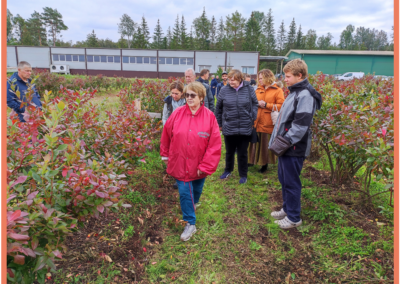 """Owner of company """"Arosa-R"""" Ltd. in front and participants of Field day in blueberries field"""